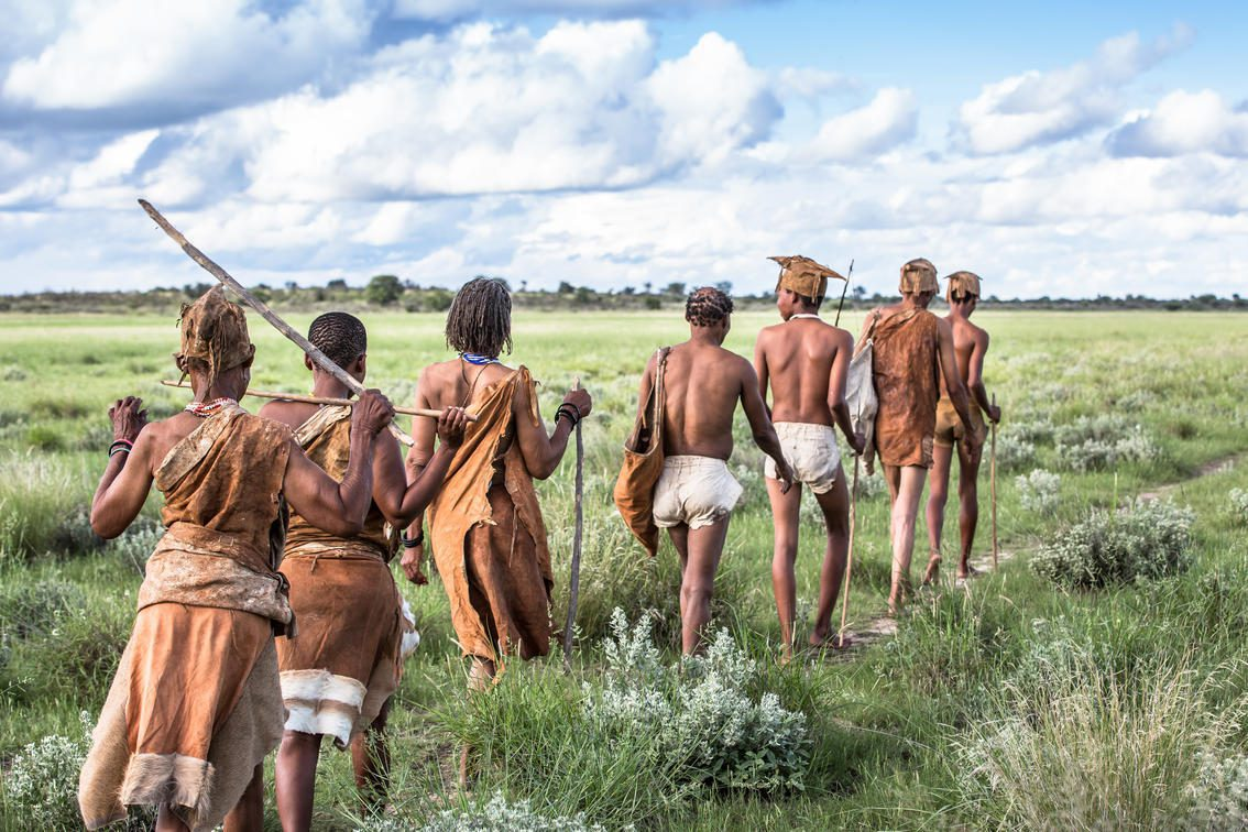 San Bushmen walking in a line across the Kalahari Plains