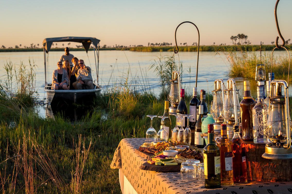 Guests arrive at a surprise sundowner spot by boat along the Linyanti River at DumaTau.