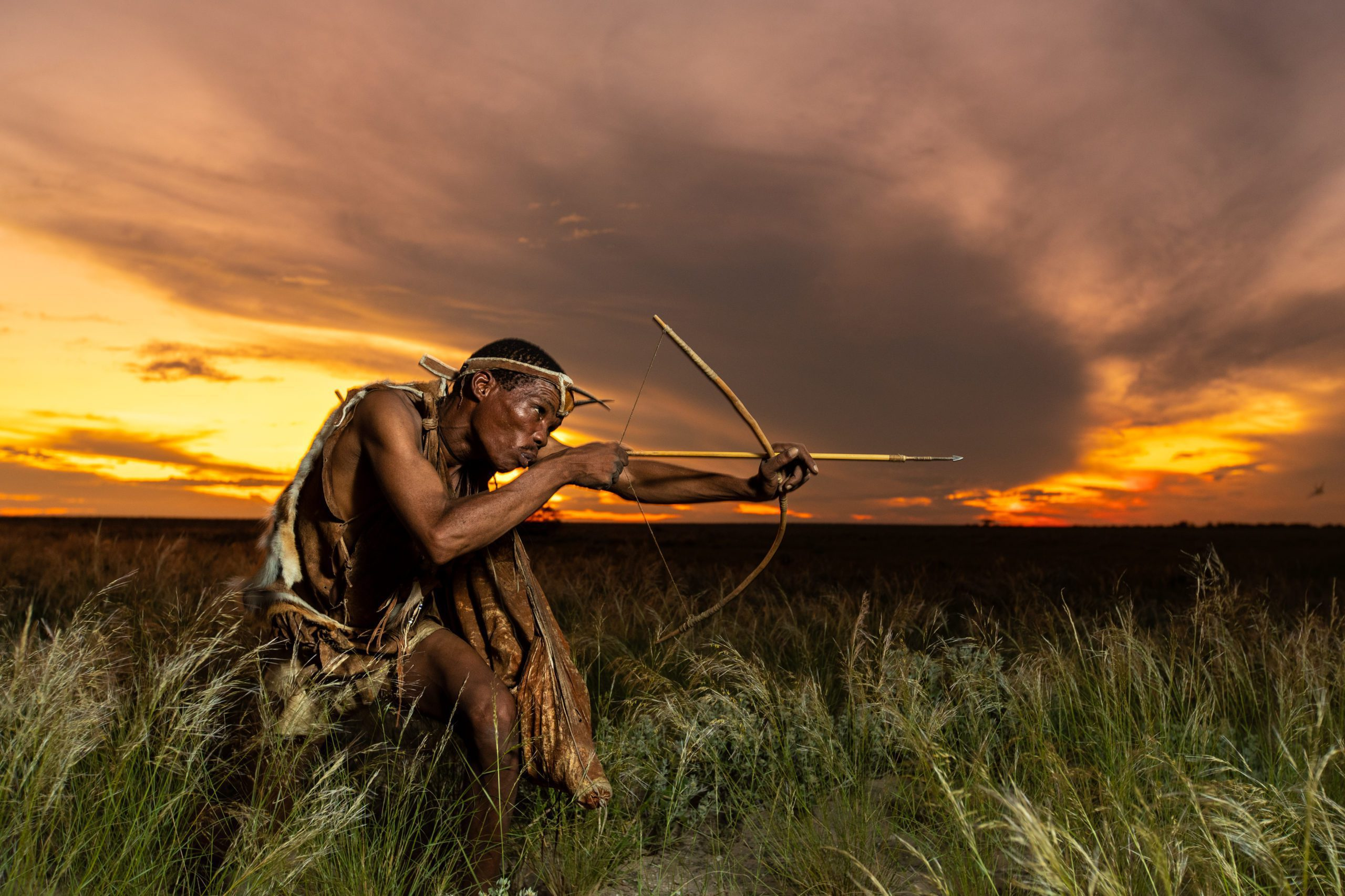 San Bushman with bow and arrow during sunset at Kalahari Plains Camp