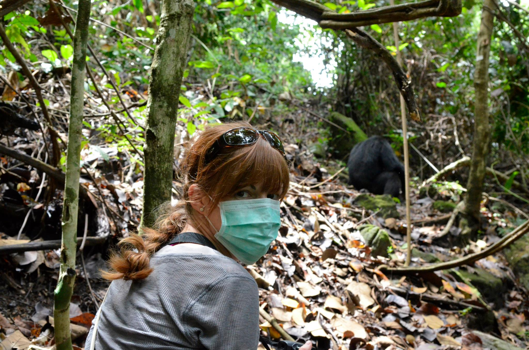 Kim in mask observing chimpanzees in Mahale Mountains