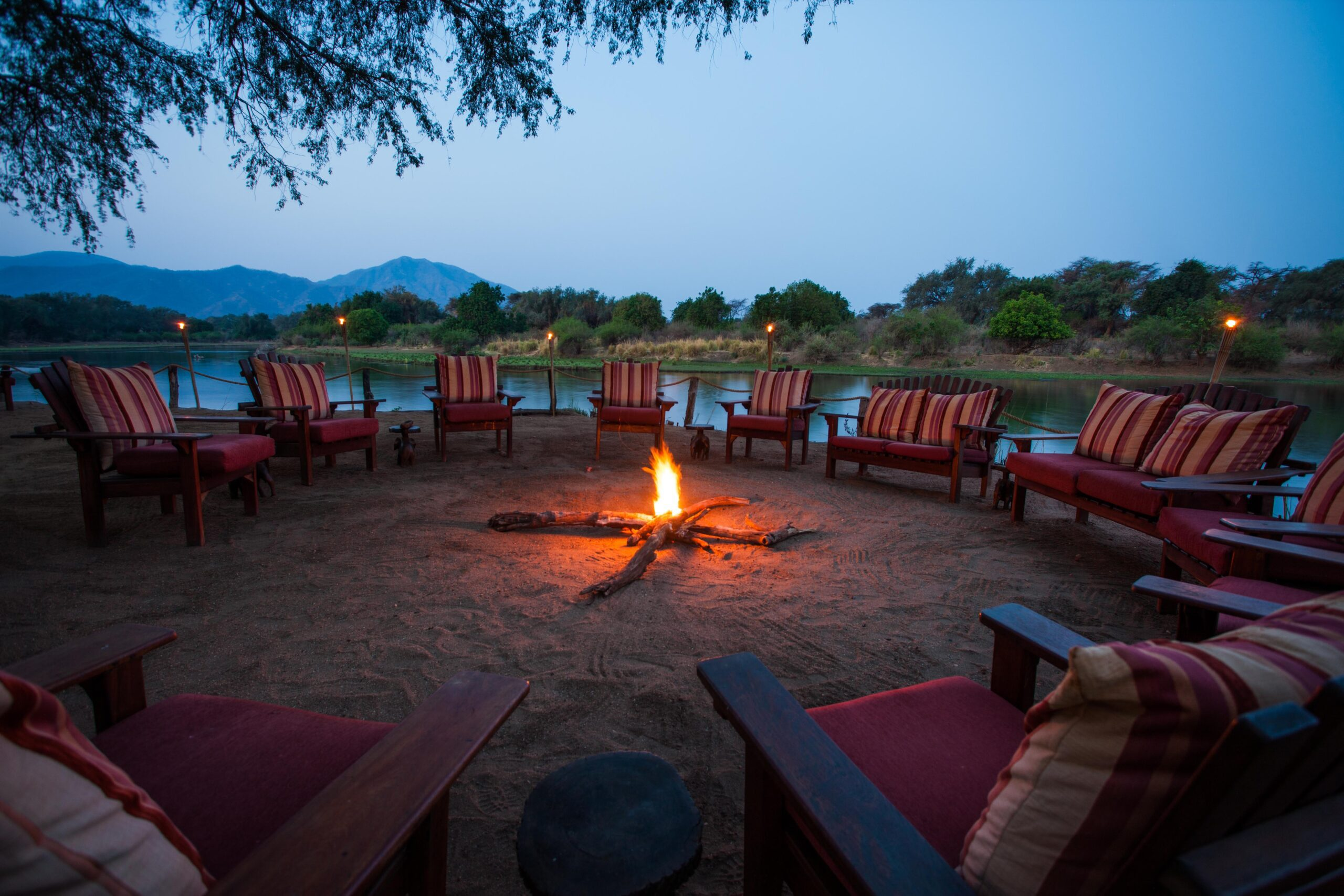 campfire surrounded by empty chairs with the river in the background at Chongwe River Camp