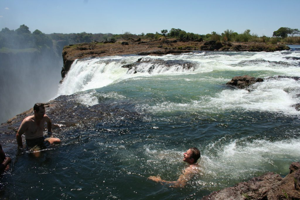Man swimming out to edge of falls at devil's pool, livingstone island, victoria falls