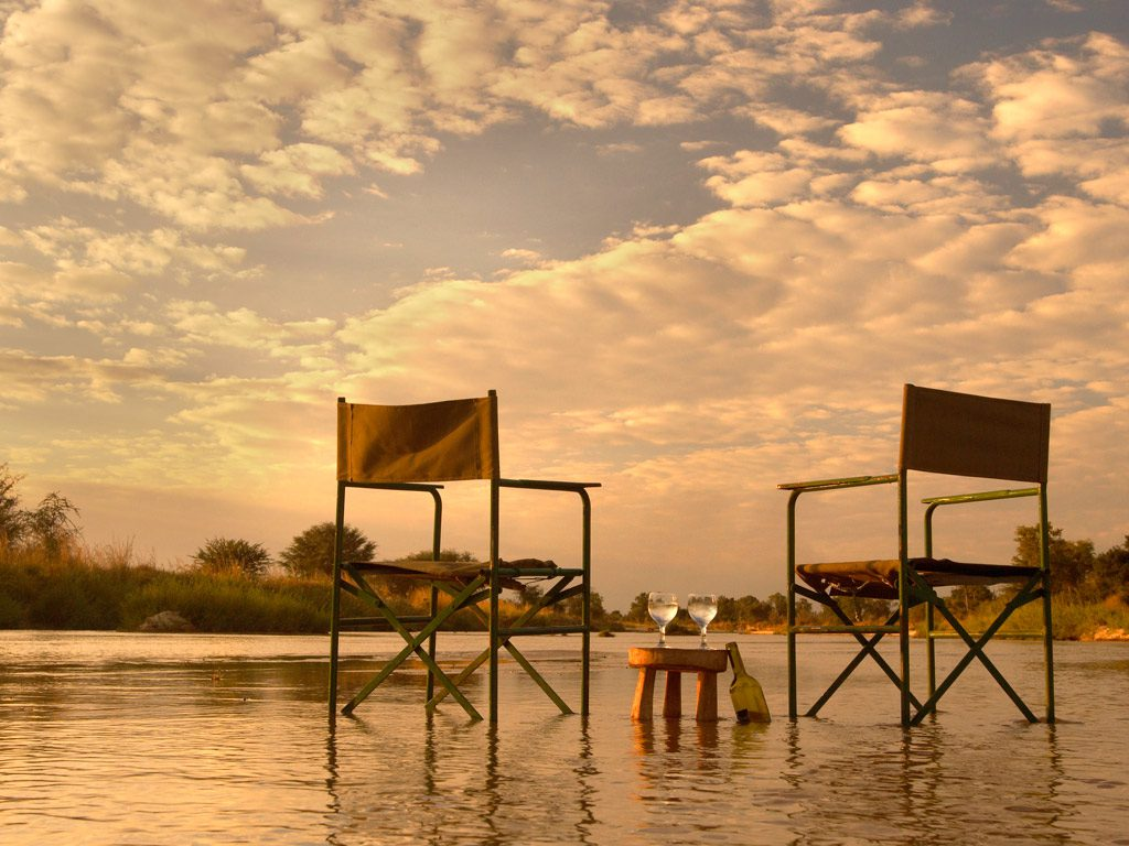 empty camp chairs and a table in the water set for sundowners at mwaleshi camp