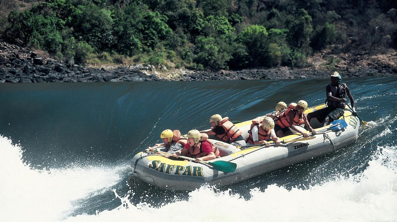 raft with rafters along bank of zambezi