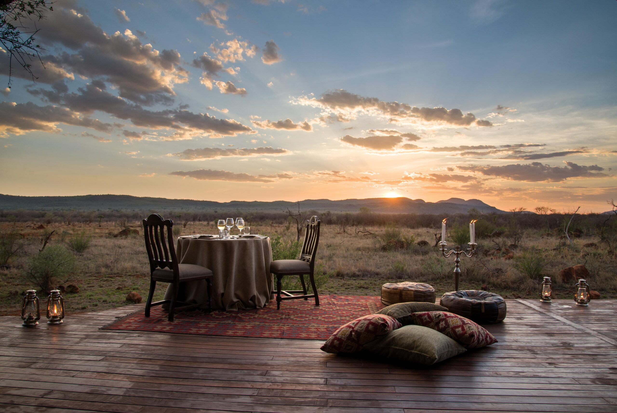 beautiful private dinner option with dining table and pillows set up at sunset madikwe hills in madikwe