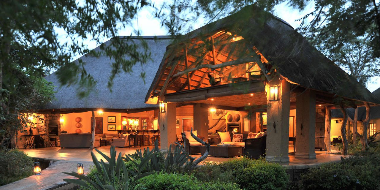 savanna lodge lit at night, seen through the trees on Southern Africa romantic safari