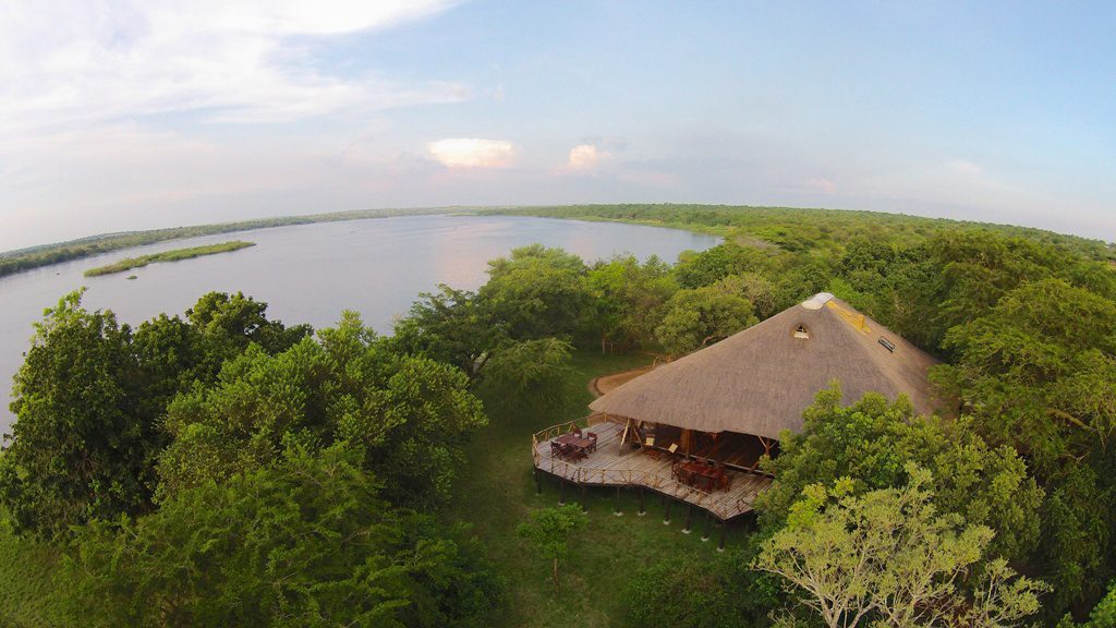 aerial view of Baker's Lodge tucked into the green trees on the bank of the Nile River viewed on our extraordinary Uganda safari