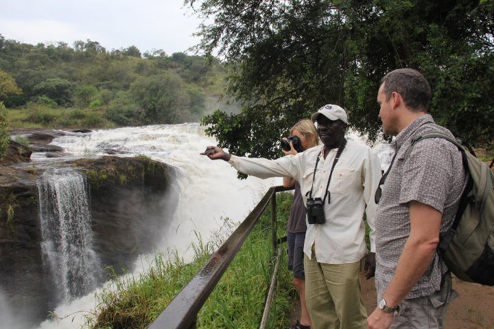 Ugandan guide sharing history with guests at the top of Murchison Falls