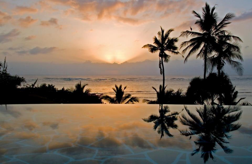 infinity pool at Alfajiri reflecting the sunset and palm trees