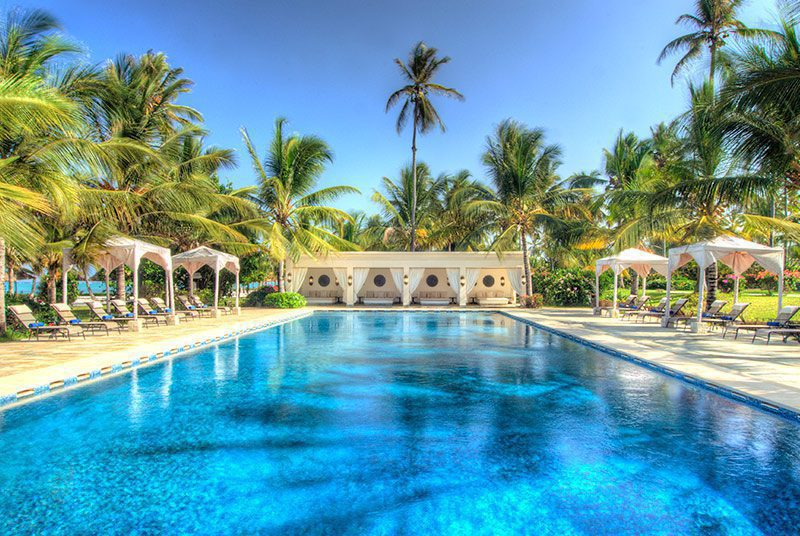 wide view of pool at baraza with chairs and palm trees