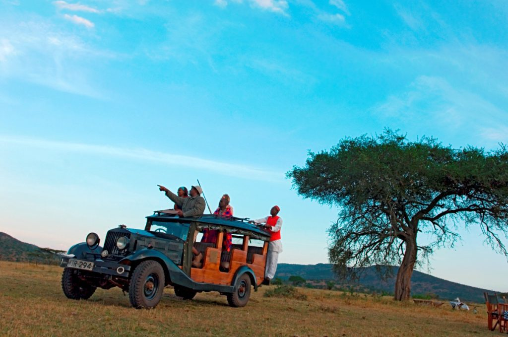 1920's car loaded with people drives across the Mara while they visit kenya
