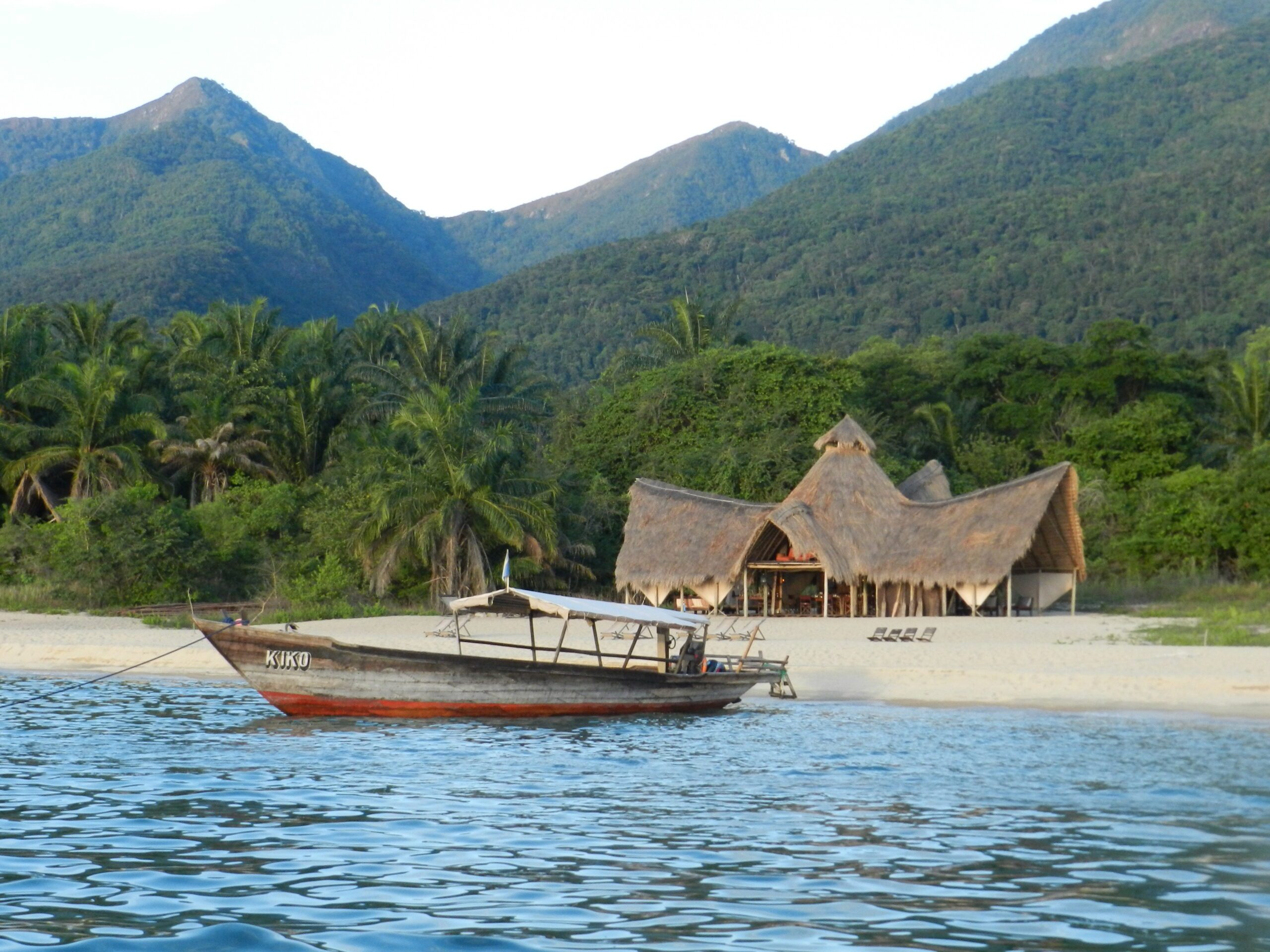 dhow boat in the water in front of Greystoke's main lodge with Mahale Mountains behind