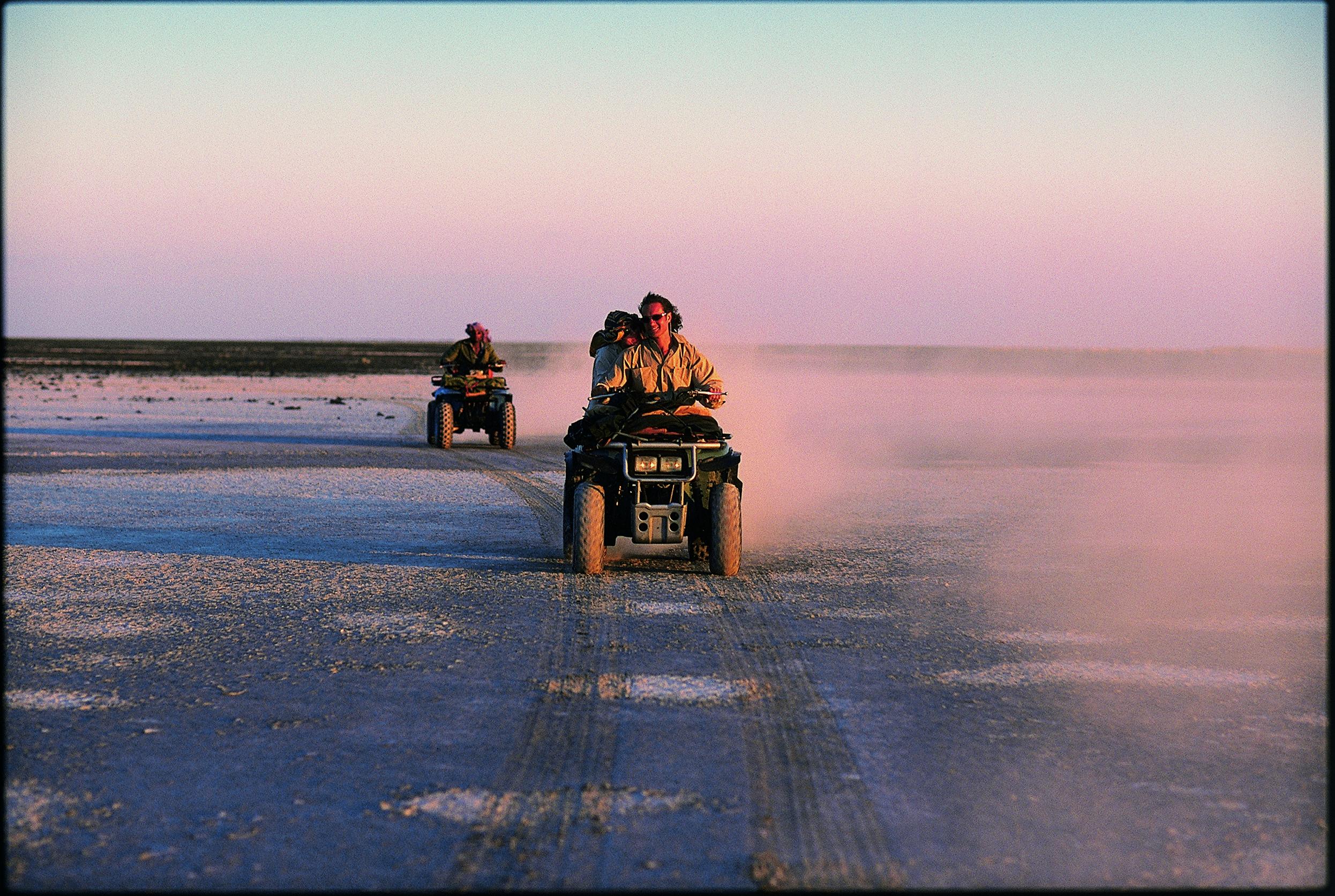 two ATVs cross the Makgadikgadi Pans in Botswana at sunset