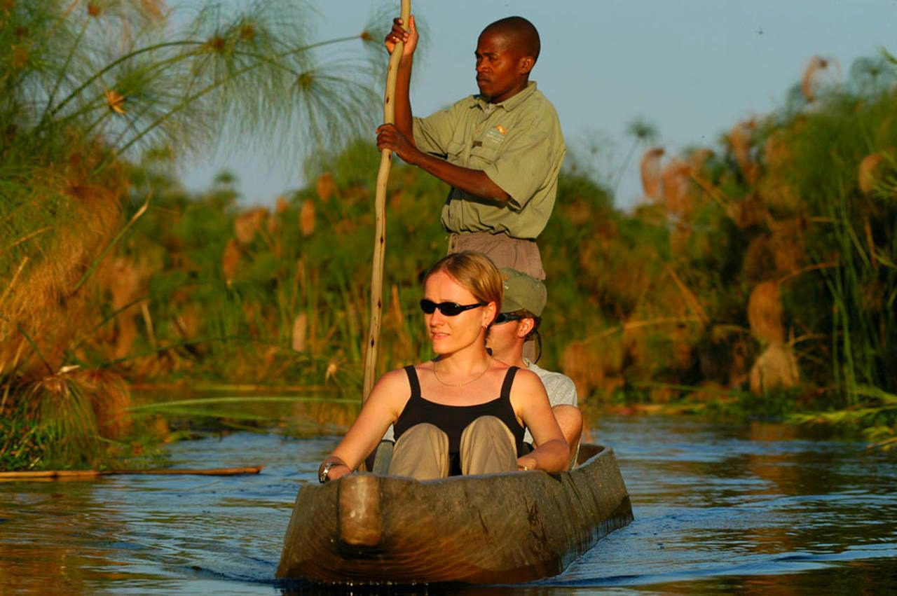 two people in a mokoro with a poler propelling them through the water of the Okavango Delta
