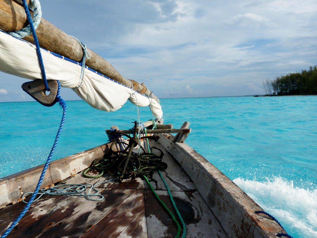 bow of Zanzibar dhow boat with tip of mast sailing in aqua blue waters