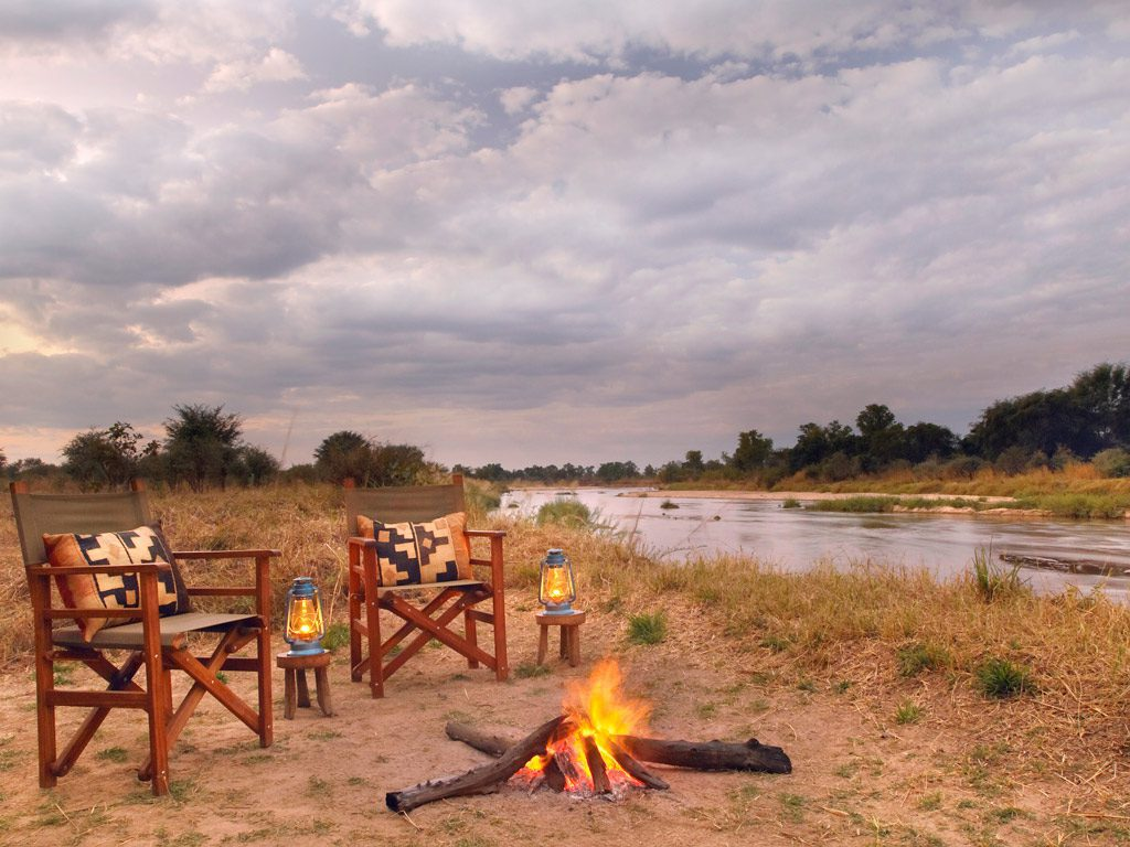 empty camp chairs and a campfire along a river at mwaleshi camp
