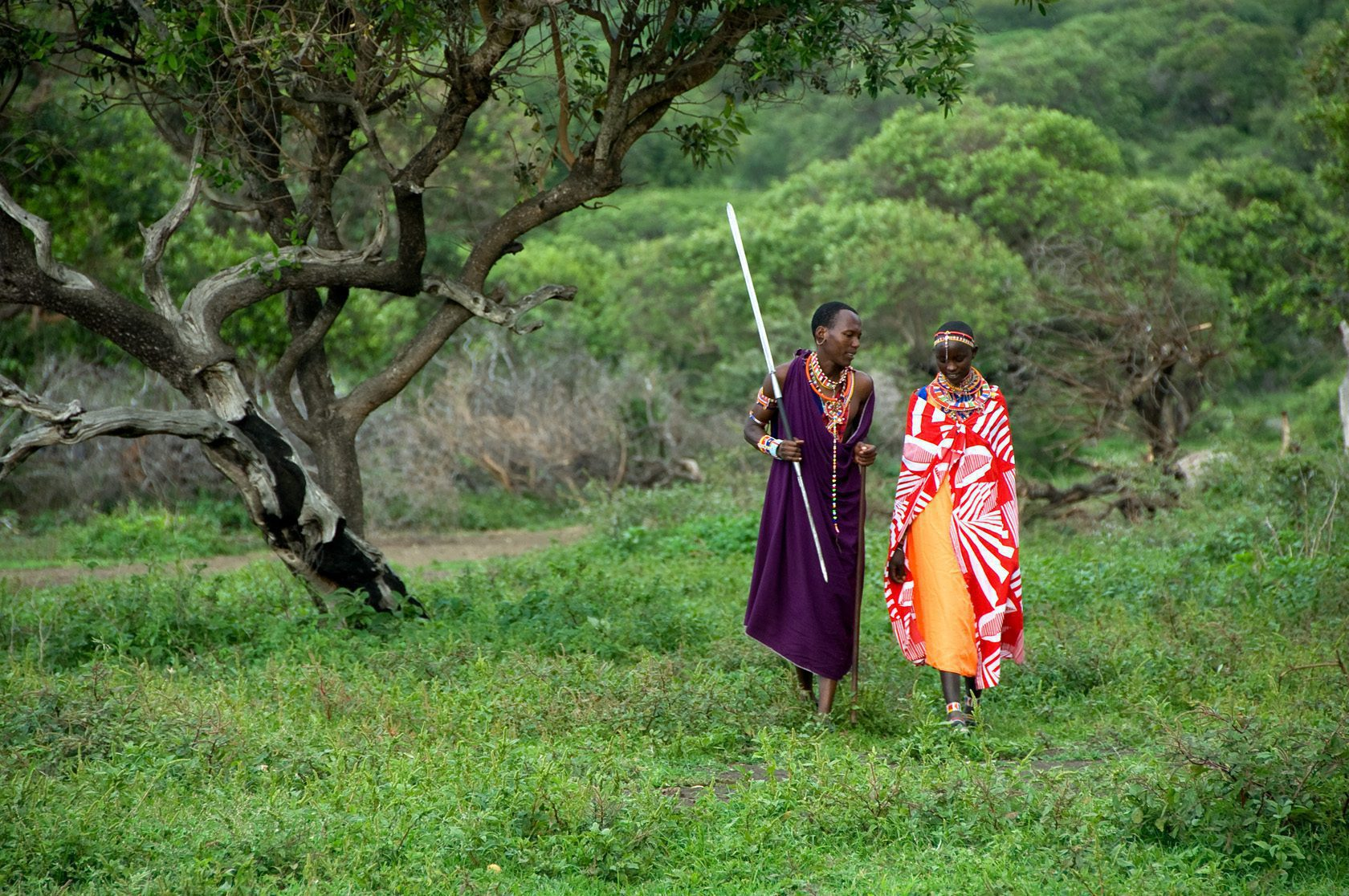 two traditionally dressed people walking in the plains near Ol Donyo Lodge