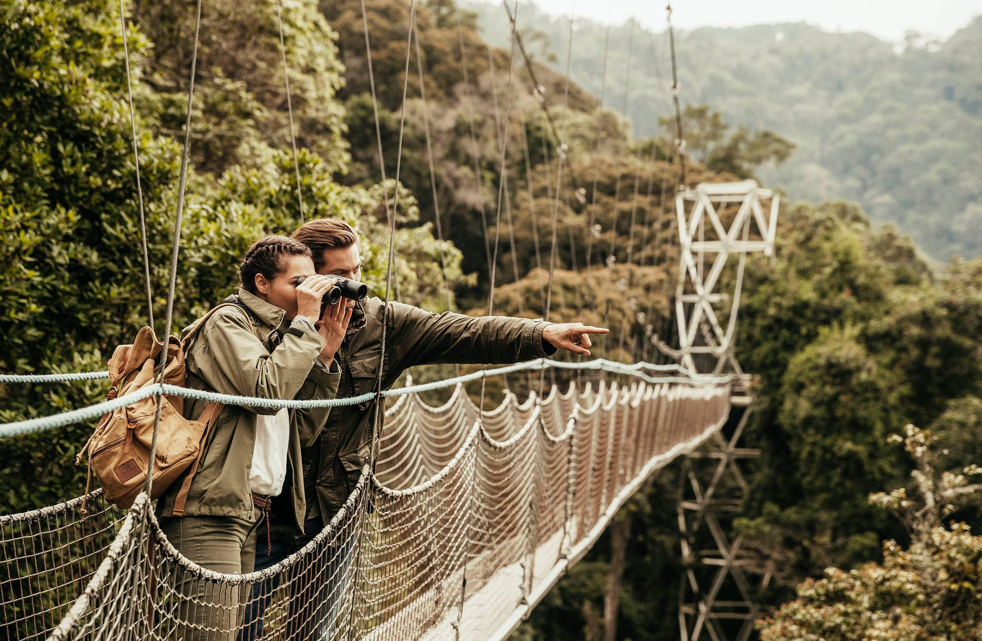 couple viewing and pointing from canopy at Nyungwe