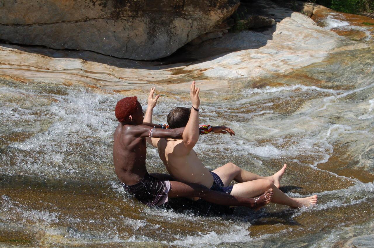 sarara camp staff sliding down the rock pools in the Mathews Range