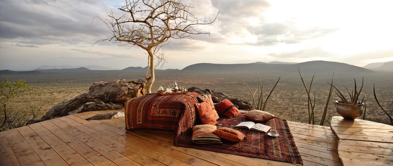 blanket and bean bag chairs set up for sundowner drinks overlooking Samburu with a tree in the mid-foreground