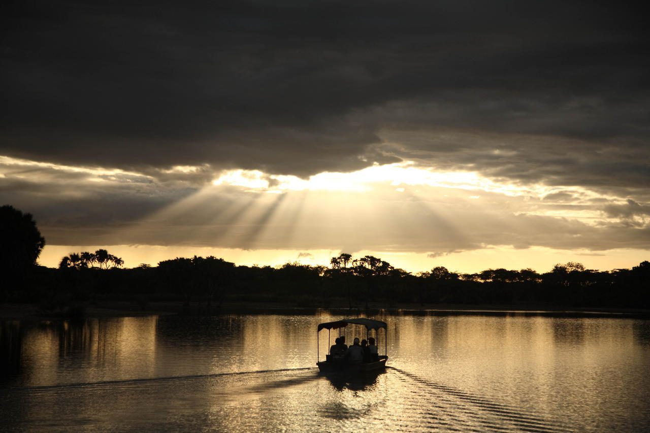 boat leaving a wake in the water heading towards the sunset peaking through the clouds