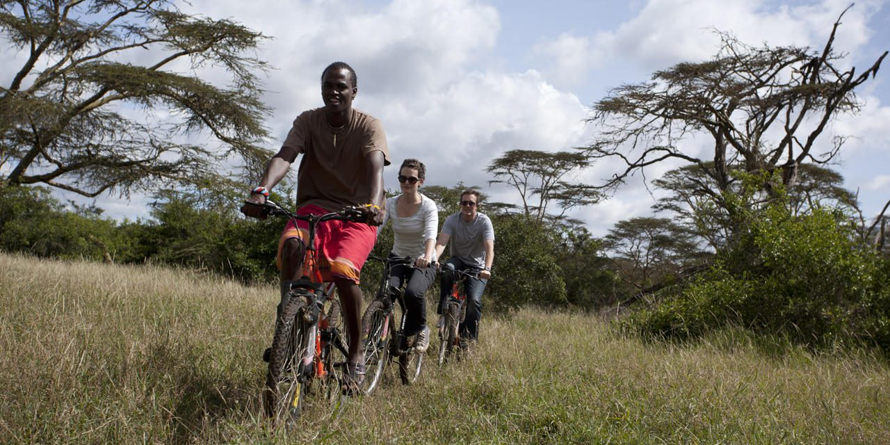 three people biking through Solio Ranch in Laikipia, Kenya