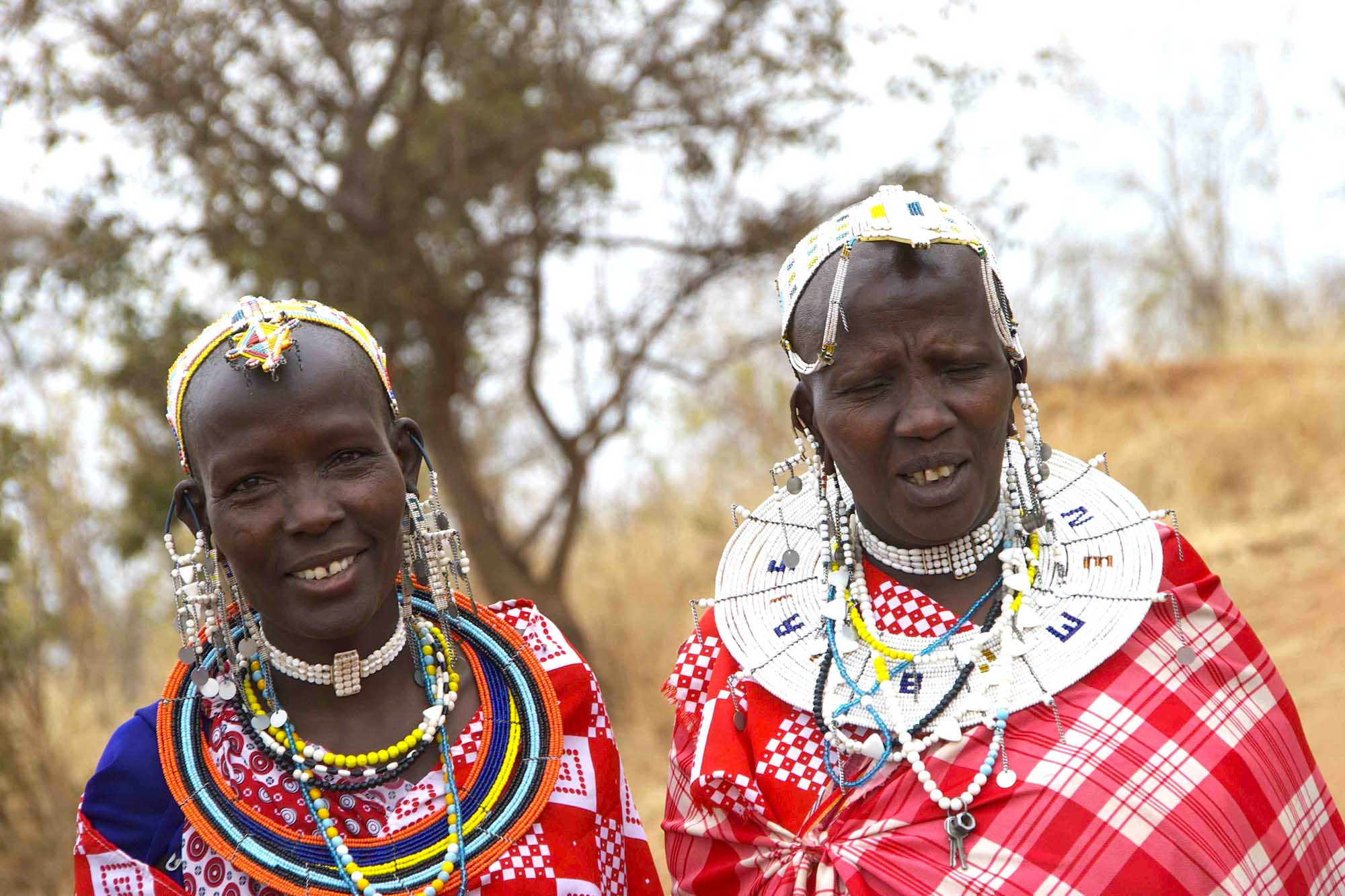 two Maasai women in brightly colored cloaks and beaded jewelry