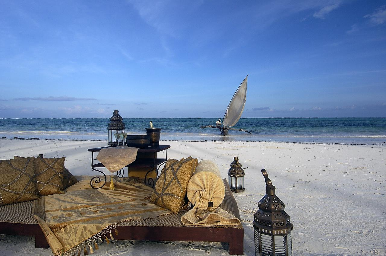 benches and lanterns set up on the sandy beach dhow boat in the water behind