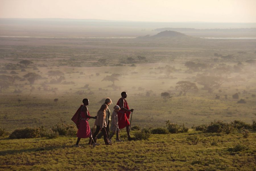 two people walking with a Masai guide look over the low clouds to a hill in the distance