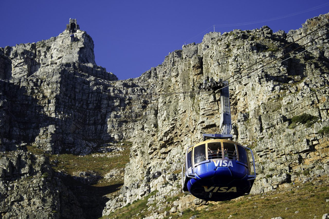 blue and yellow cable car coming down table mountain during the day in cape town, south africa