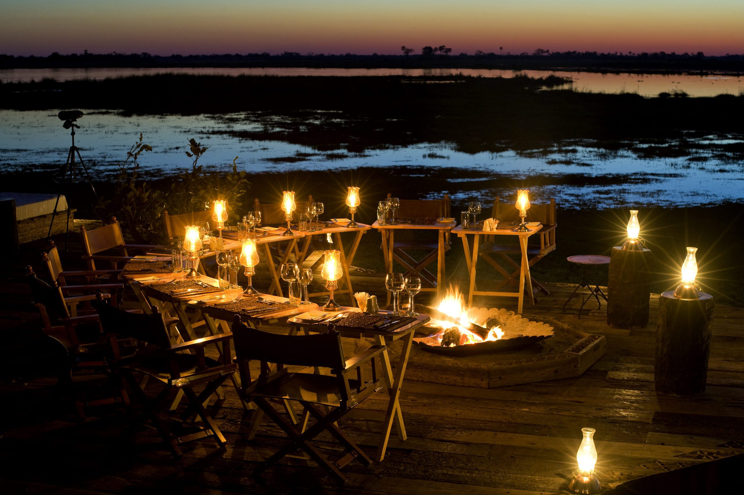 Firelit tables down along the lagoon at Zarafa, preparing for a beautiful al fresco dinner.