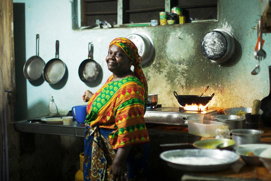 Zanzibar woman dressed in brightly colored clothes and standing in her kitchen with a cast iron pan over a flame