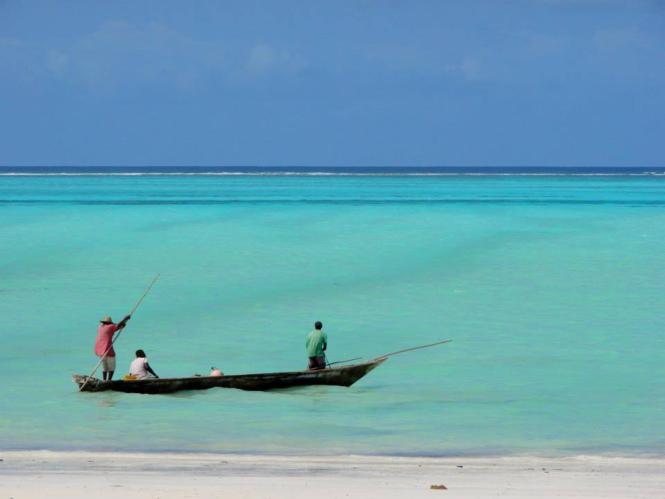 one dhow with three fishermen on aqua water in zanzibar