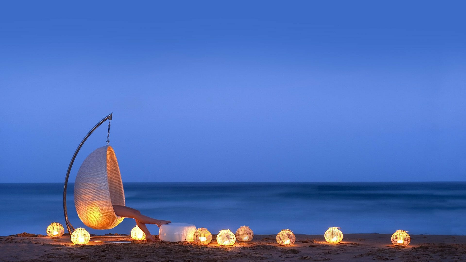 woman in a pearl shaped chair sits on the beach with lanterns at night