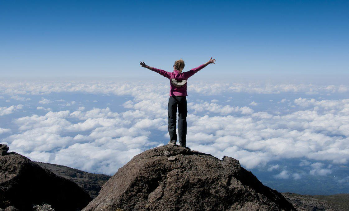 hiker with her arms outstretched and standing on a rock at the top of Mount Kilimanjaro towering above the clouds