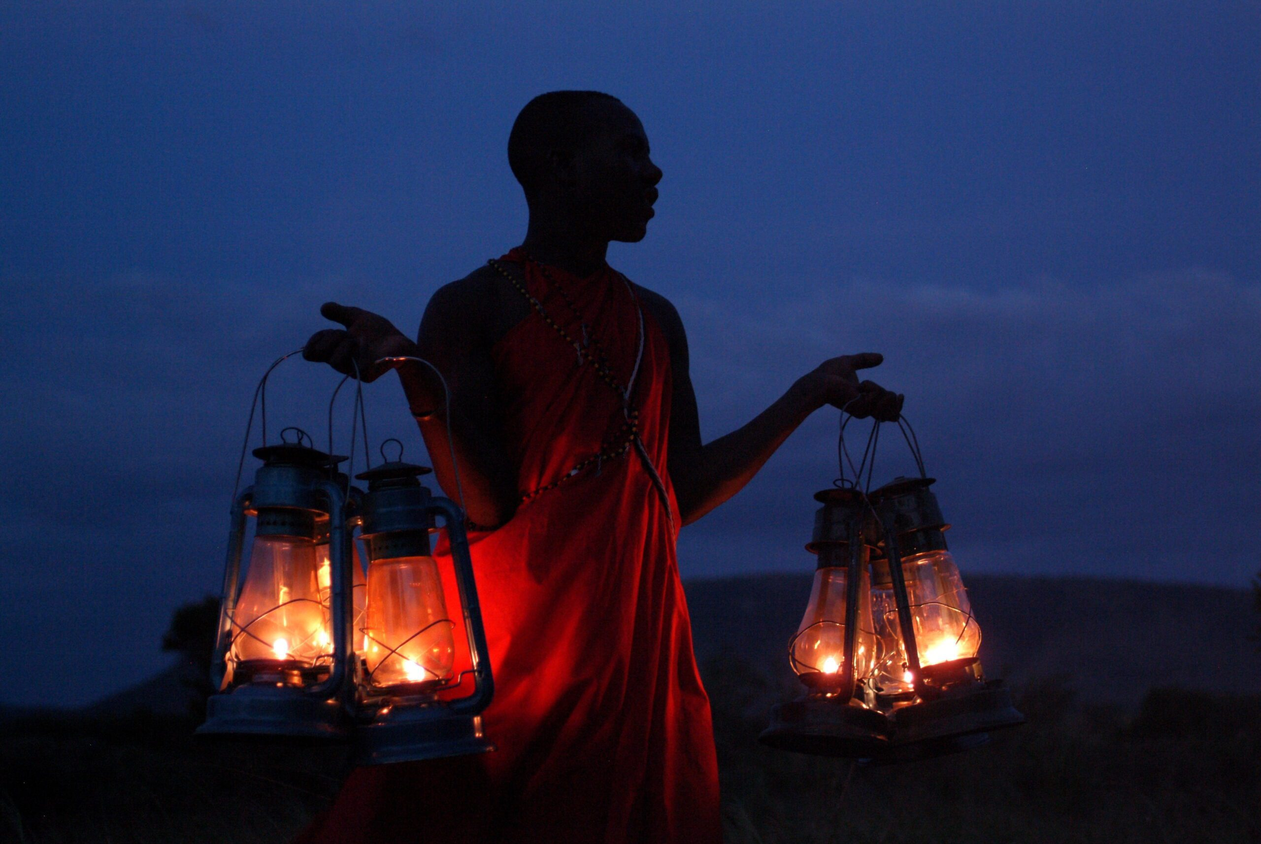 masai warrior carrying lanterns at night seen on our adventure Kenya safari