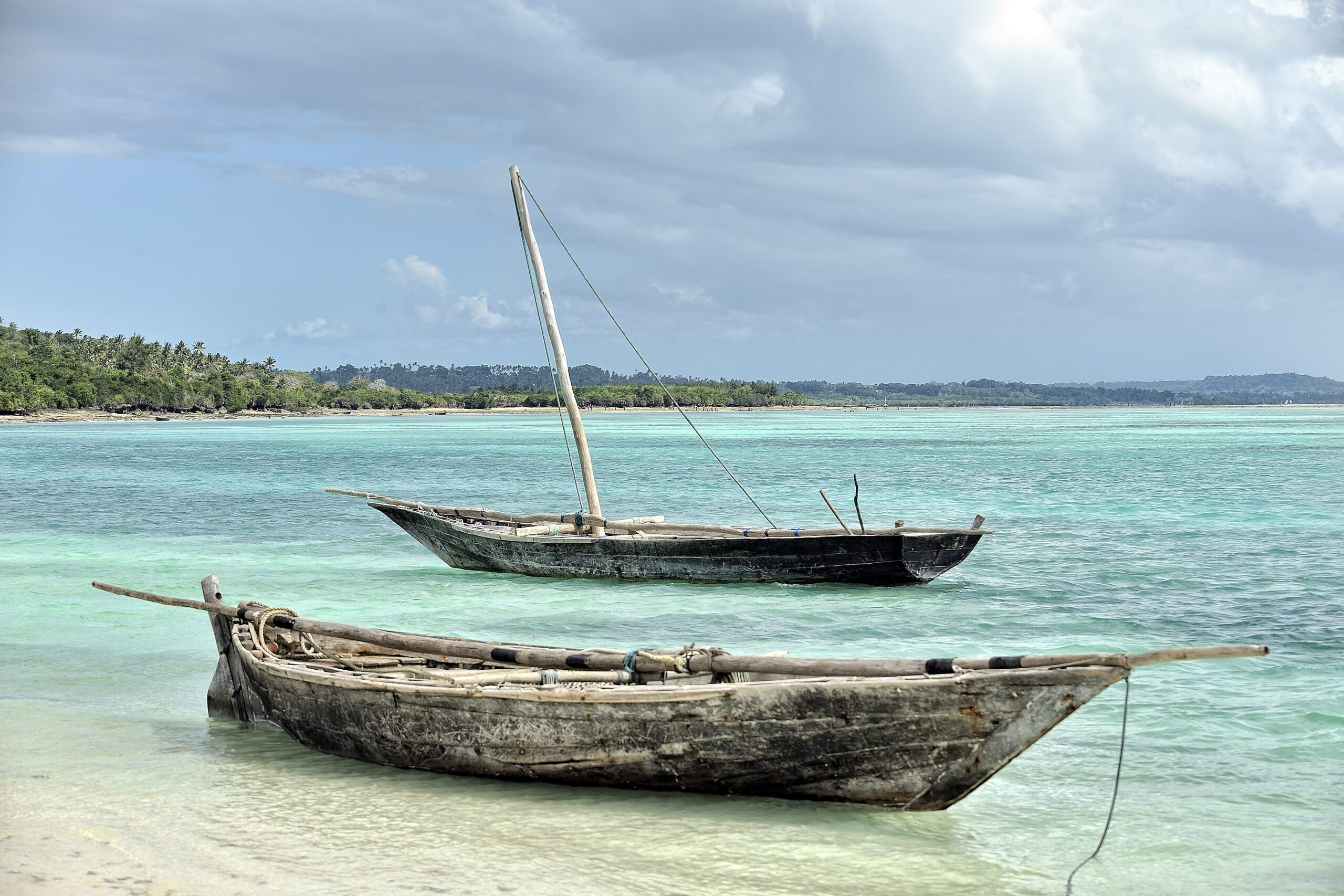 two fishing dhows in turquoise water on white sandy beach