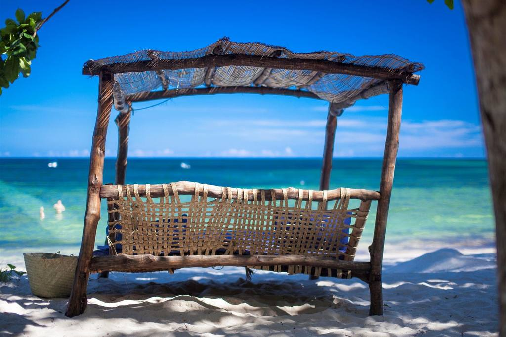 Kinondo Kwetu bench swwing overlooking the aqua waters on a white sand beach