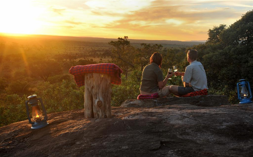 couple sitting on a rock drinking wine at sunset on our Tanzania big game safari