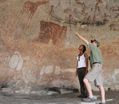 guide points to rock art in cave with guest