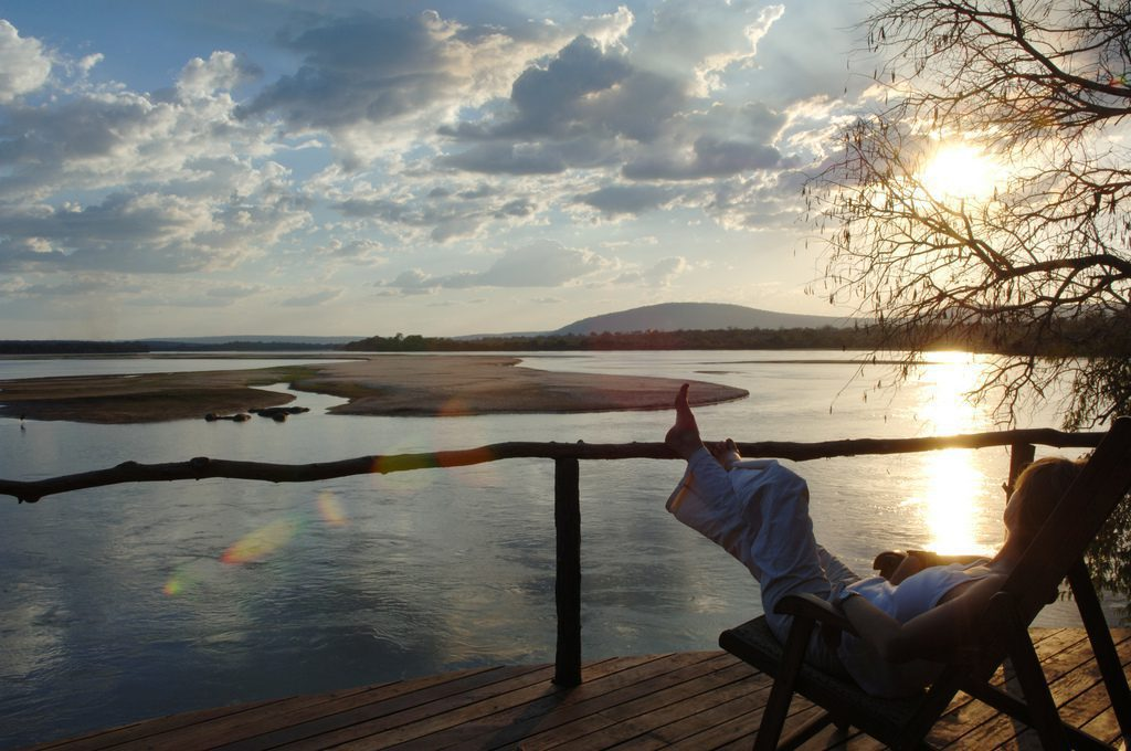 guest relaxing on a wooden deck over looking the river at sunset with puffy white clouds above