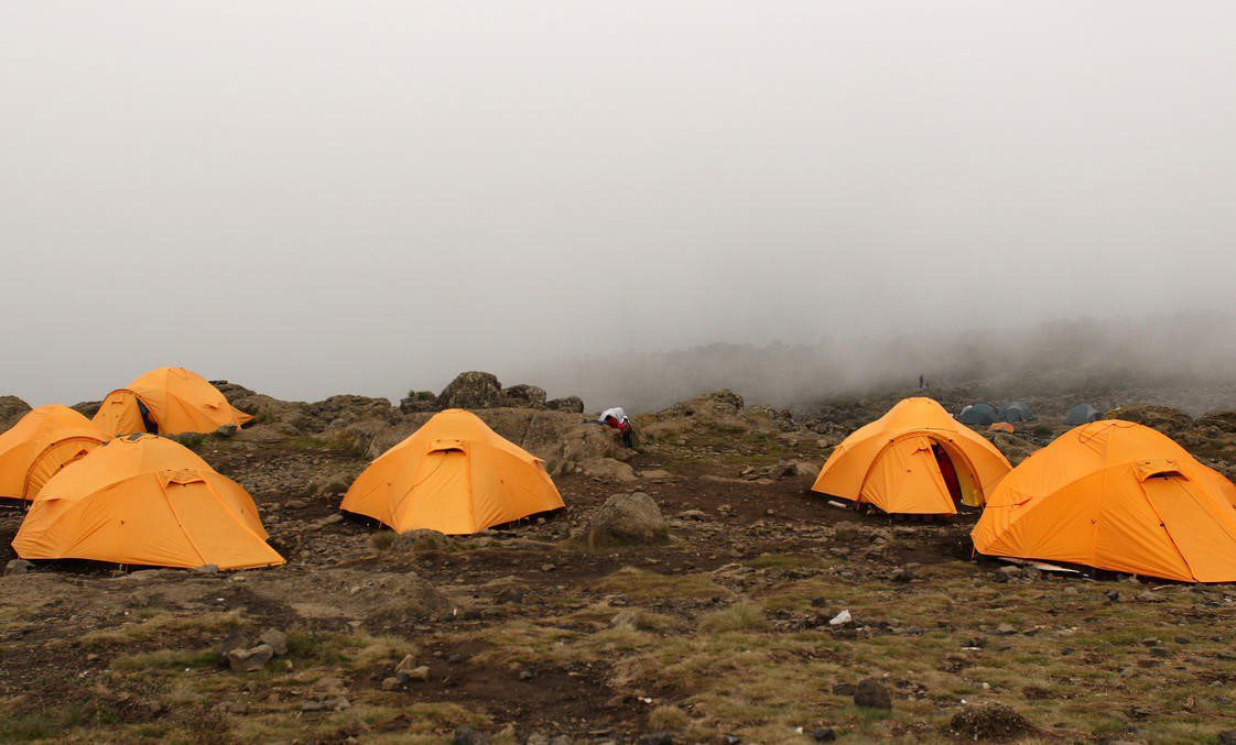 group of yellow dome tents on the dirt ground under a shroud of fog on Mount Kilimanjaro