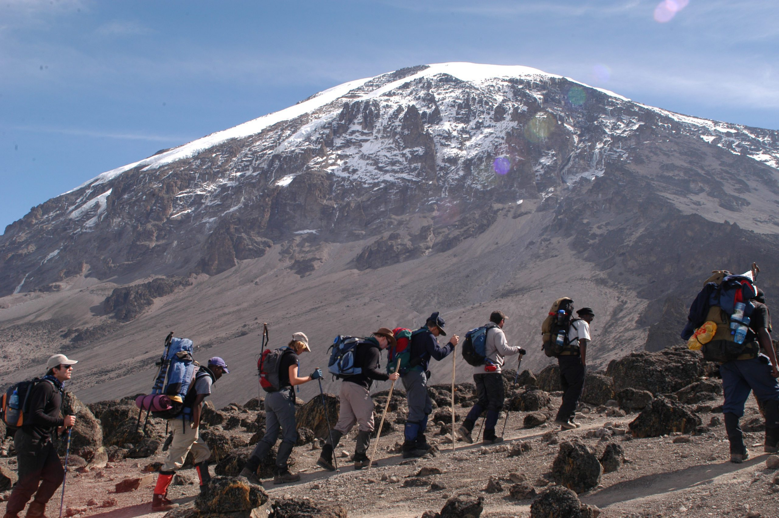 row of hikers with backpacks and walking sticks following the trail on Kilimanjaro with the snow-capped peak in the distance