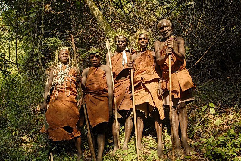 Five Batwa people in traditional dress standing in the forest seen on Uganda Safari