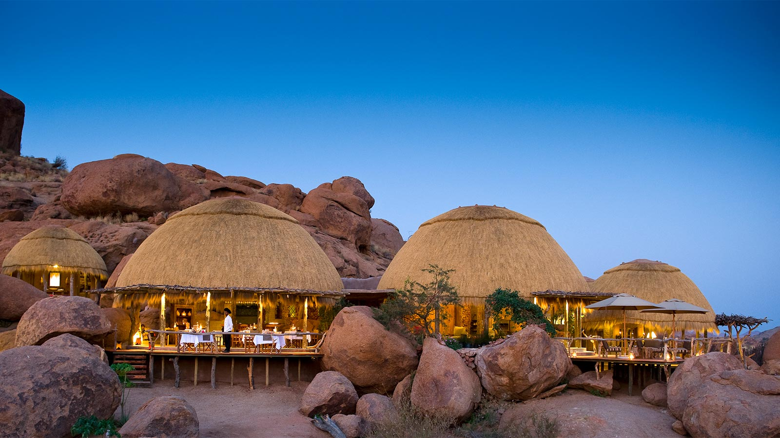 on our best Namibia safari you'll see domed thatch roofs of Camp Kipwe at sunset