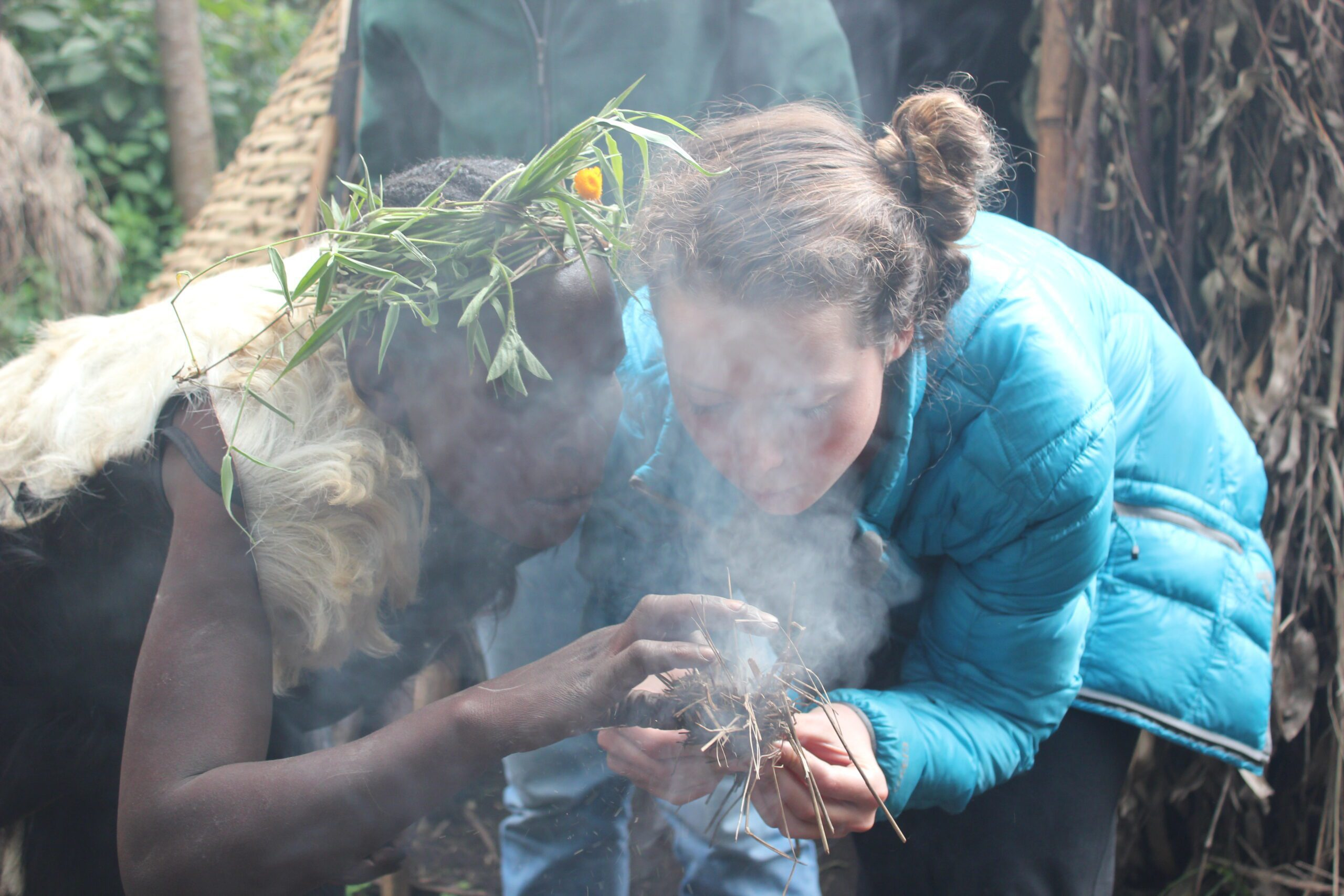 smoke is rising from sticks as a guest in a turquoise jacket helping a local Batwa make fire Uganda Safari