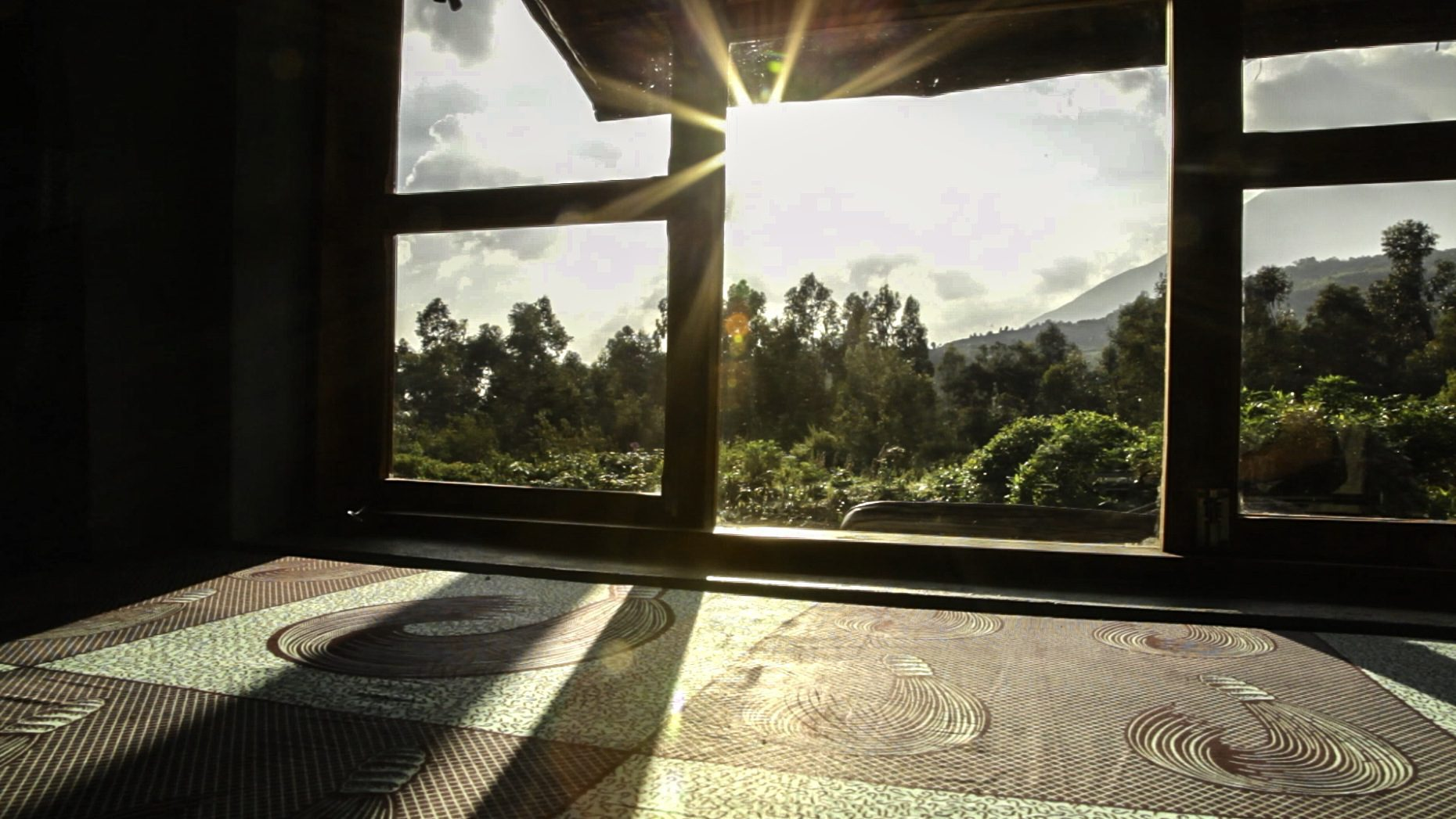 views through the window of a banda at Mount Gahinga Lodge with the sunlight peering through the clouds