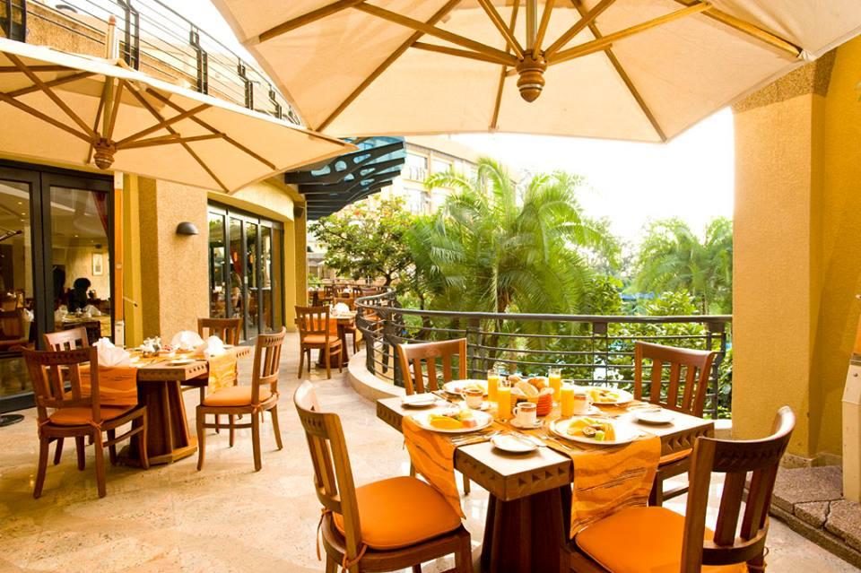tables under umbrellas on the patio at Kigali Serena part of Rwanda safari