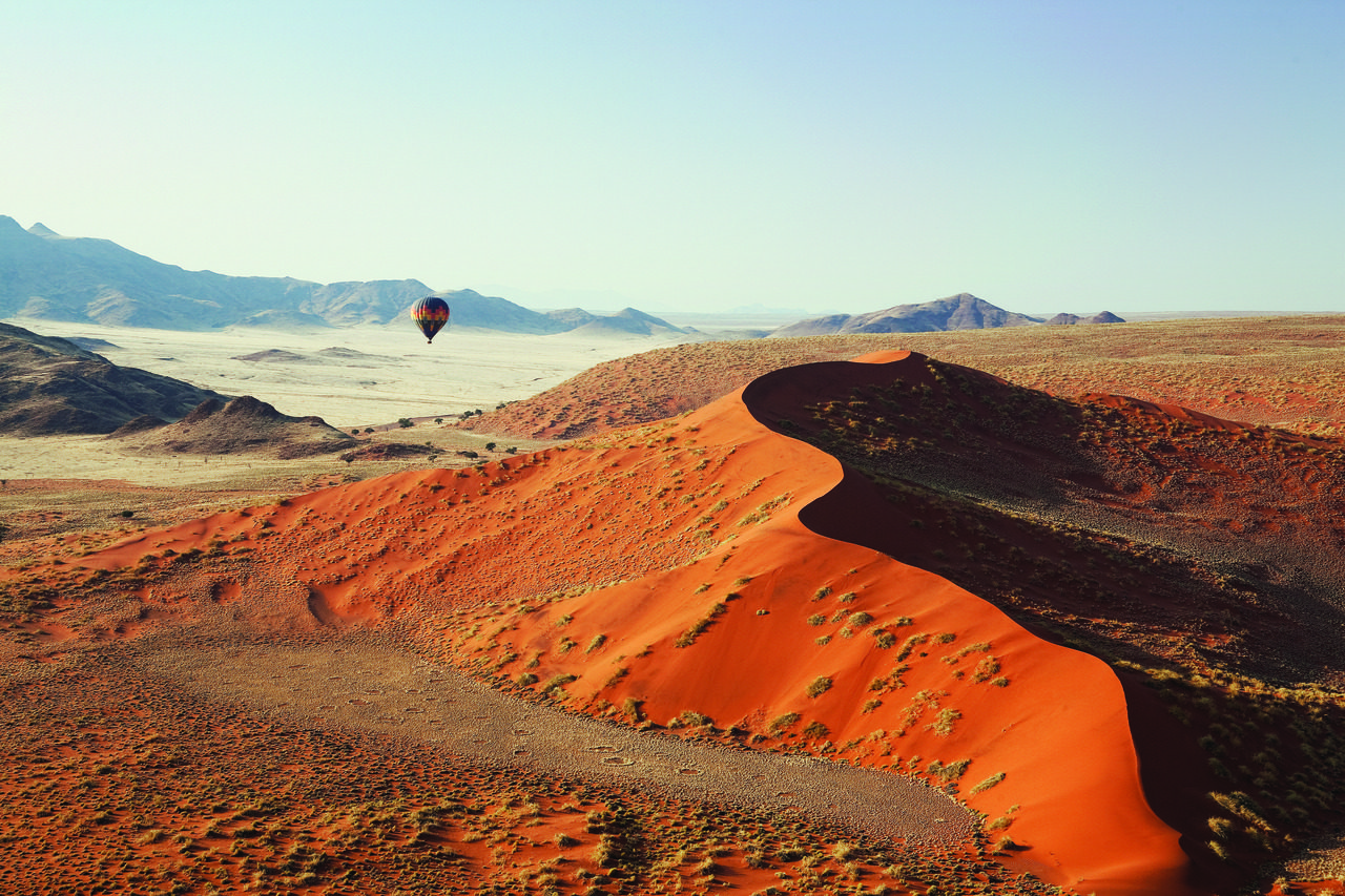 Sossusvlei dunes at sunrise and hot air balloon soaring above