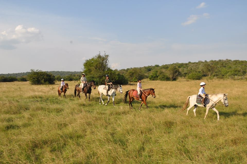horseback riding in a line through the open plains in Lake Mburo National Park